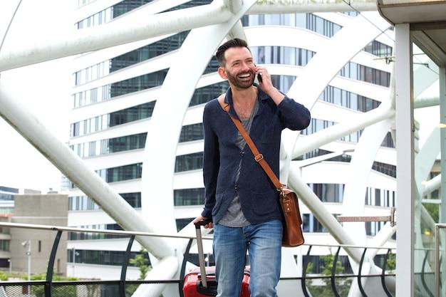 Voyage homme marchant avec valise et parler au téléphone mobile
