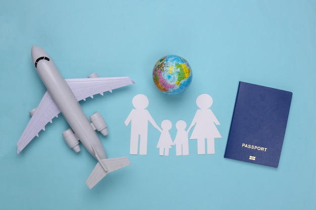 Voyage ou immigration familiale. famille de papier ensemble, avion, globe et passeport sur un bleu.