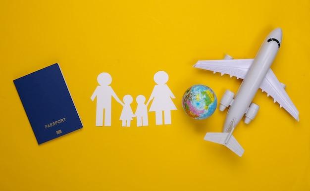 Voyage ou immigration familiale. famille de papier ensemble, avion, globe et passeport sur jaune.
