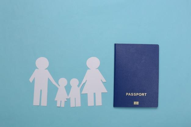 Voyage ou immigration familiale. famille de papier ensemble et passeport sur un bleu.