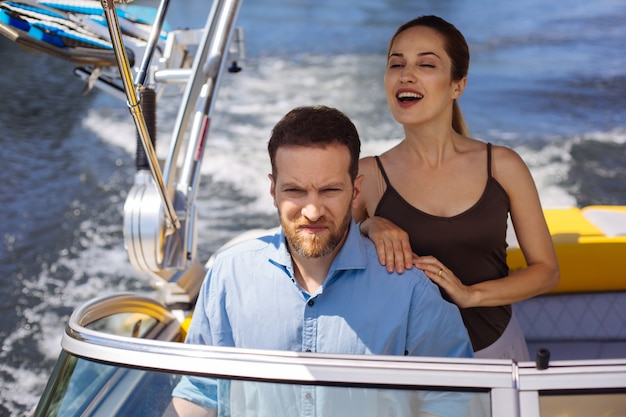 Voyage d'inauguration. charmante jeune femme souriante joyeusement et son mari plissant les yeux de la lumière du soleil tout en testant un nouveau yacht ensemble