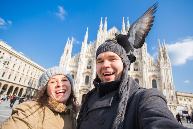 Voyage, italie et concept de couple amusant - touristes heureux prenant un autoportrait avec des pigeons devant la cathédrale duomo, milan