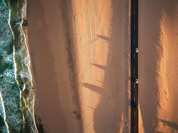 Voyage léger au coucher du soleil avec concept de voiture - belle vue aérienne de la côte avec l'océan et la plage de sable et route droite noire avec des personnes voyageant en véhicules - mode de vie et nature de l'errance