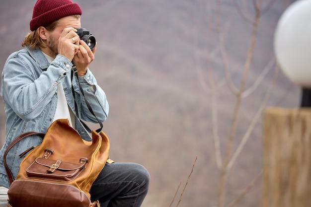 Voyage masculin avec sac à dos en cuir à l'aventure en prenant des photos sur des paysages de haute montagne.