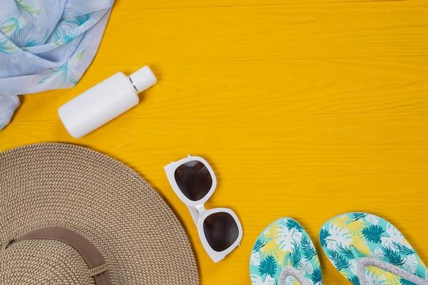 Voyage en mer, chapeau, lunettes de soleil, lunettes, sandales posé sur un plancher en bois jaune.