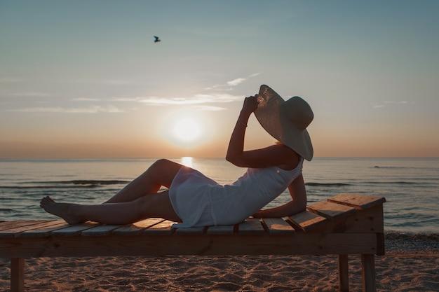Voyage à la mer une fille en robe et chapeau marche le long de la plage un touriste se promène