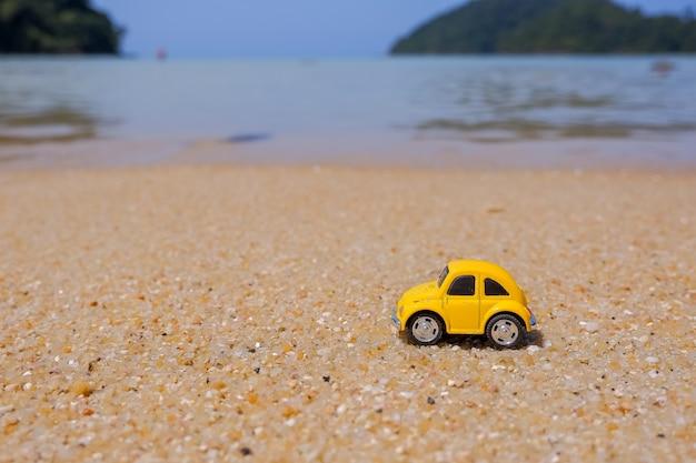 Voyage à la mer, petite voiture jaune sur la plage. concept de vacances et de tourisme carte postale avec petit