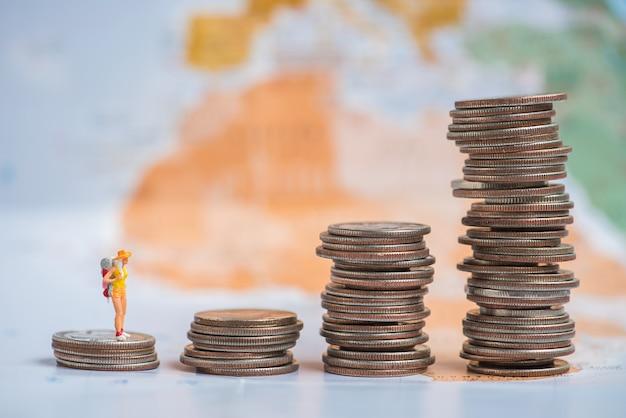 Voyage miniature femme debout sur la pile de pièces de monnaie avec fond de carte du monde