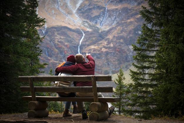 Voyage en montagne. la famille dans les montagnes est assise sur un banc et regarde les montagnes