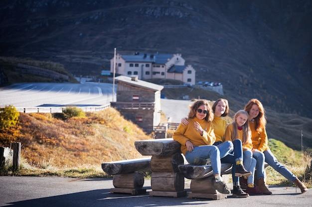 Voyage en montagne. une famille heureuse dans les montagnes est assise sur un banc