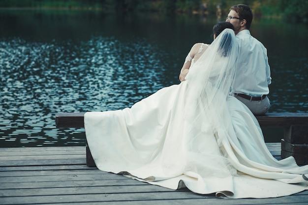 Voyage de noces. les mariés s'embrassant sur la rive du lac.