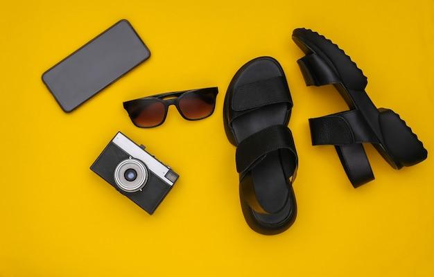 Voyage à plat en aboyant. sandales, lunettes de soleil, appareil photo et smartphone sur fond jaune. vue de dessus