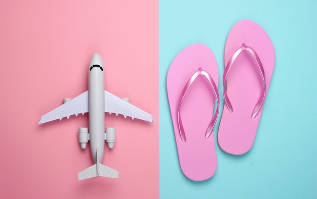 Voyage à plat composition. figurine d'avion, tongs sur pastel bleu rose.