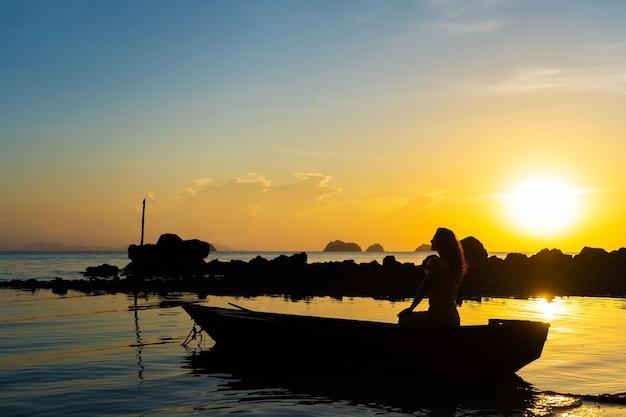 Voyage romantique en bateau avec une fille au coucher du soleil. la fille est assise dans un bateau en bois sur l'océan.