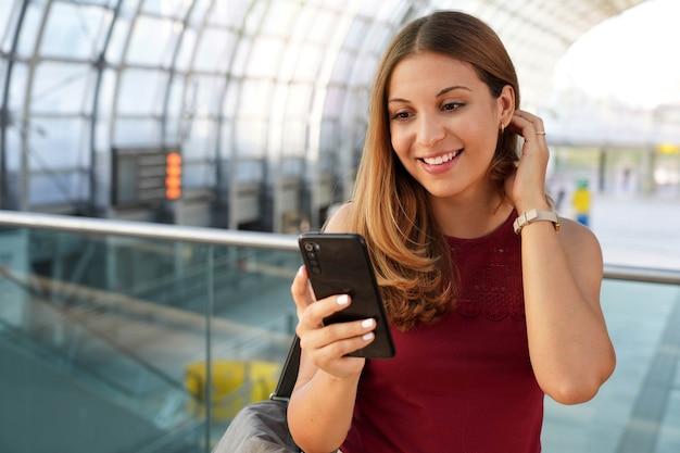 Voyage et technologie. jeune femme enthousiaste recevant de bonnes nouvelles sur son smartphone en attente d'embarquement dans le terminal de l'aéroport.