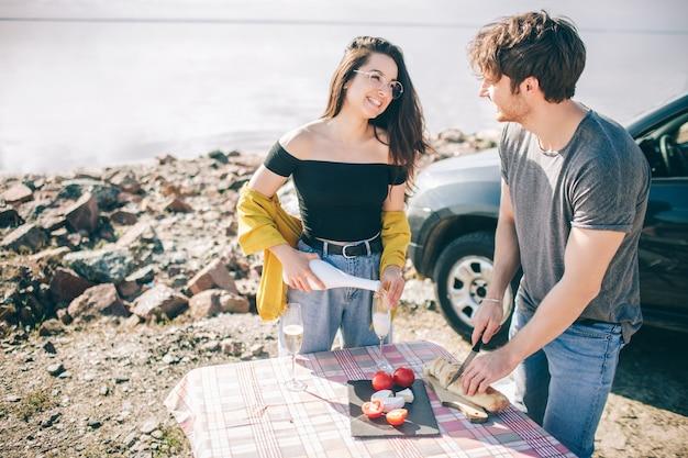 Voyage, tourisme - un homme et une femme boivent du champagne près de l'eau sur une table portable pliante. pique-nique près de l'eau. couple à l'aventure. concept de voyage en voiture.