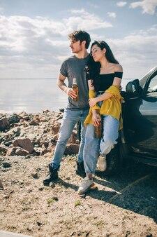 Voyage, tourisme - pique-nique au bord de l'eau. couple à l'aventure. concept de voyage en voiture. l'homme et la femme boivent de la bière.