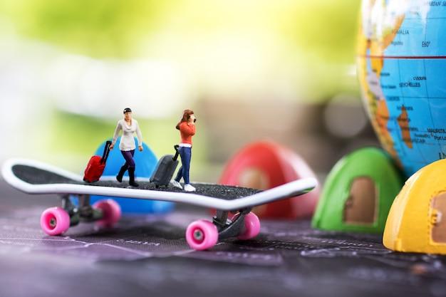 Voyage à travers le monde et l'aventure. gens miniatures avec bagages marchant sur planche à roulettes avec globe et lit de tente.