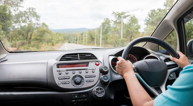 Voyage en voiture avec les mains du conducteur sur le volant