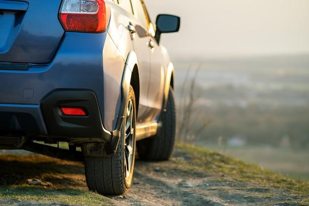 Voyager en auto, aventure dans la faune, expédition ou voyage extrême sur une voiture suv. détail de la voiture hors route bleue au coucher du soleil, véhicule 4x4 hors route dans le champ au lever du soleil.