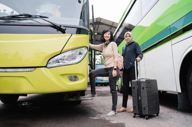 Voyager en bus. une femme aux cheveux courts avec un casque et une femme dans un foulard portant une valise derrière elle en allant en bus
