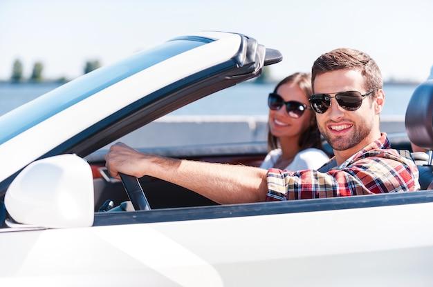 Voyager avec confort. heureux jeune couple profitant d'un voyage sur la route dans leur cabriolet blanc tout en regardant la caméra et en souriant