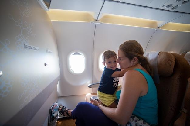 Voyager avec un enfant. mignon bambin embrasse maman alors qu'il était assis dans le siège passager de l'avion.