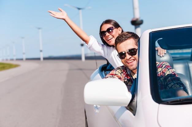 Voyager avec plaisir. heureux jeune couple profitant d'un voyage sur la route dans leur cabriolet blanc