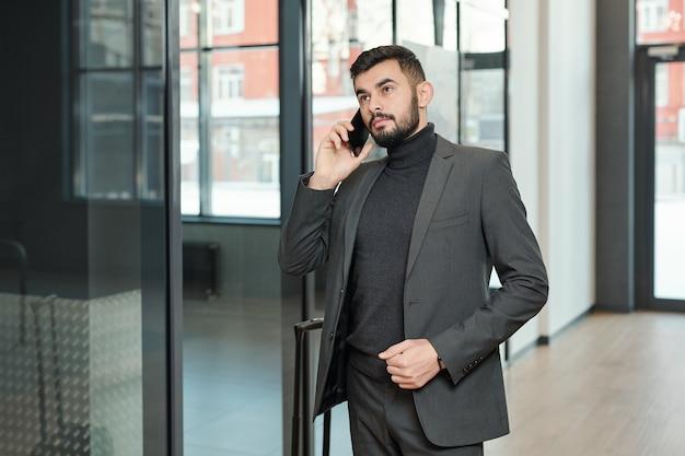 Voyageur d'affaires élégant avec smartphone et valise téléphonant à la réceptionniste de l'hôtel à l'arrivée à l'aéroport