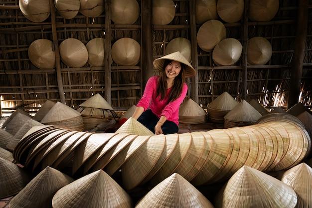 Voyageur asiatique artisan fabriquant le chapeau vietnamien dans la vieille maison