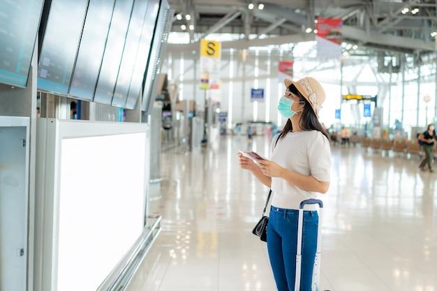 Voyageur asiatique femme avec un masque facial à l'aéroport