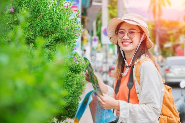 Voyageur asiatique fille adolescente ou touriste sourire heureux voyage en vacances d'été avec carte à pied dans la rue