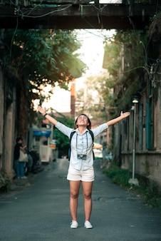 Voyageur asiatique portant une chemise en jean bleue avec sac à dos et appareil photo - happy relax on va