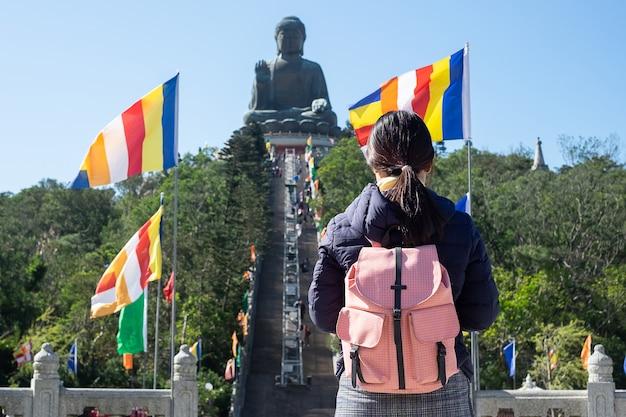 Un voyageur asiatique visite le tian tan big buddha situé sur l'île de ngong ping lantau
