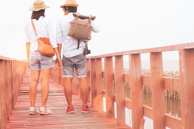 Un voyageur asiatique voyageant sur un pont de bois en bord de mer, concept love and travel