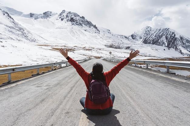 Voyageur assis et levant les bras sur l'autoroute du karakoram