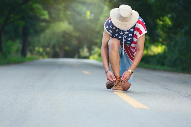 Un voyageur attache ses chaussures sur une route de campagne.