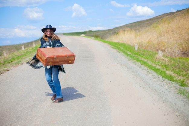 Voyageur auto-stoppeur attend voiture sur route avec valise