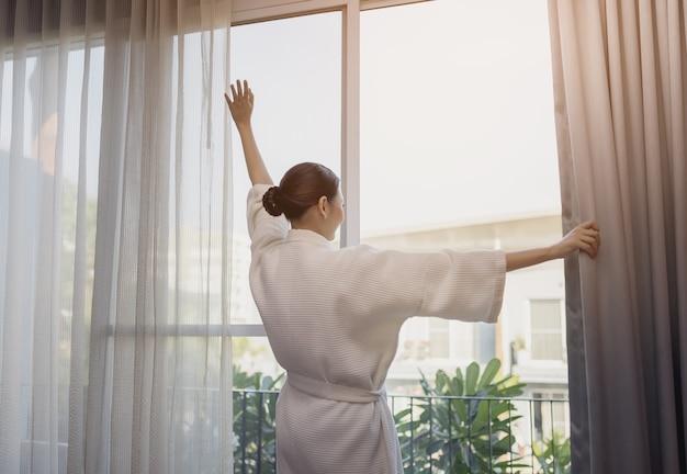Voyageur belle femme asiatique sourire à regarder là-bas rester près de la porte dans la chambre d'hôtel