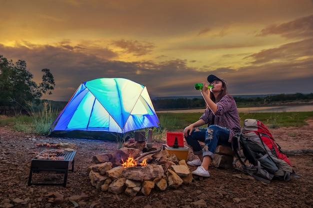 Voyageur camping sur la rivière / montagne. barbecue avec une boisson relaxante au coucher du soleil.