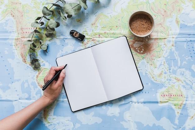 Un voyageur écrivant sur un cahier vierge avec jouet de voiture, café sur la carte