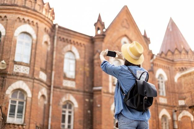 Voyageur élégant avec chapeau prenant des photos en vacances