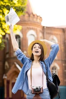Voyageur élégant avec chapeau tenant la carte locale