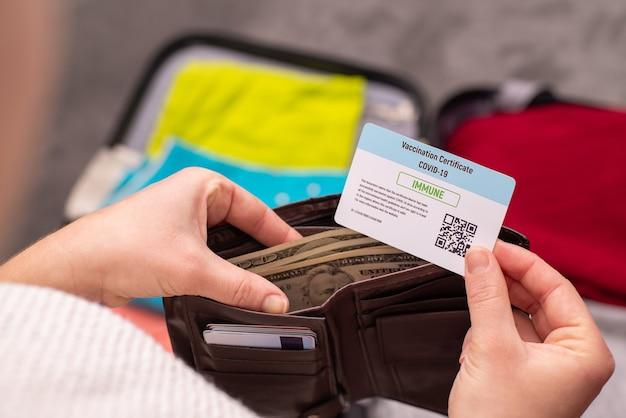Voyageur emportant un certificat de vaccination dans son portefeuille avant de partir en voyage