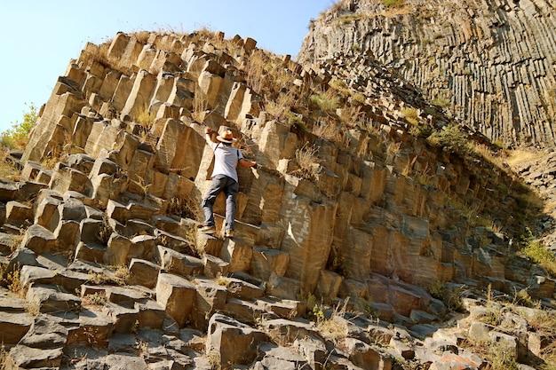 Voyageur escalade les étonnantes formations de colonnes de basalte le long de la gorge de garni, arménie