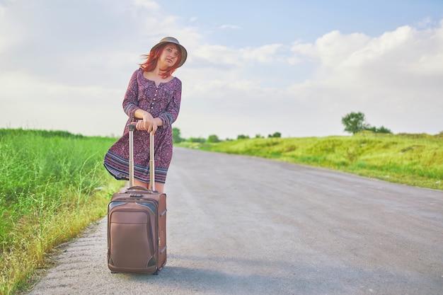 Voyageur femelle en robe d'été et chapeau faisant de l'auto-stop avec valise sur la route au printemps.
