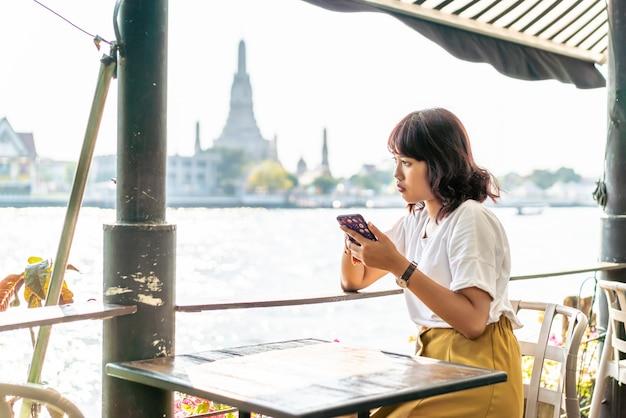 Voyageur femme asiatique à l'aide de son téléphone au café