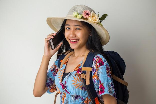 Voyageur femme asiatique parlant au téléphone mobile. concept de voyage d'été sur fond blanc