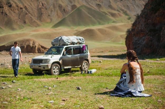 Voyageur femme assis sur l'herbe. la voiture dans les montagnes en arrière-plan.