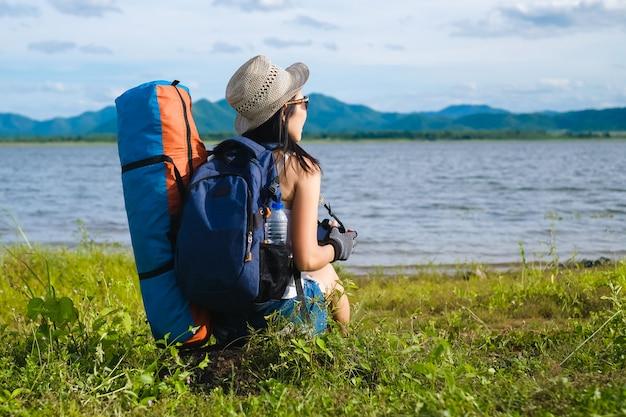 Voyageur femme assis près du fond du lac est la montagne